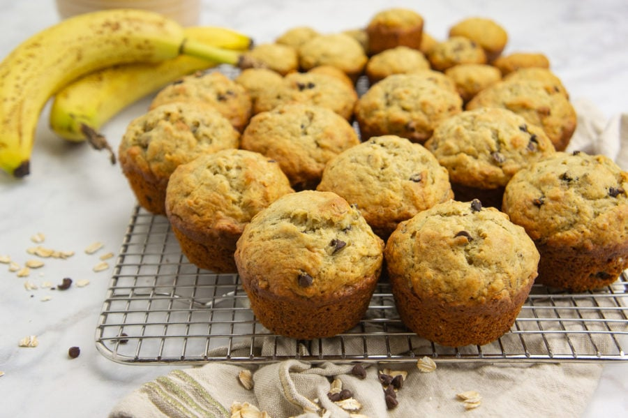 a cooling rack with muffins stacked on it beside a banana and brown linen towel