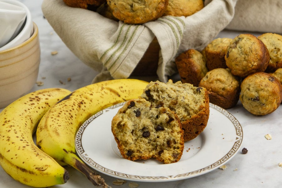 a banana oat muffin open on a white plate beside bananas