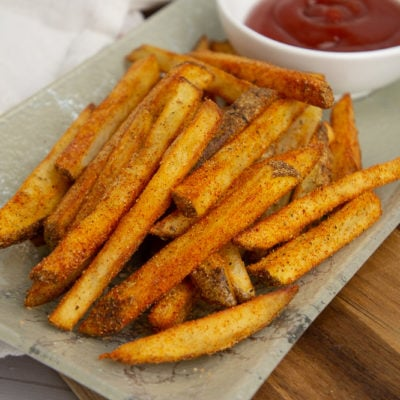 a plate of fried cajun fries with ketchup