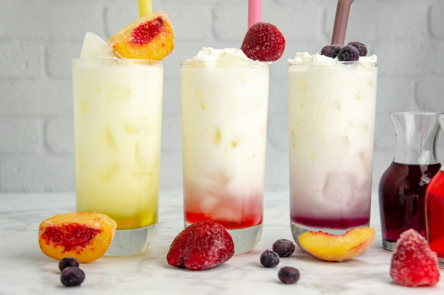 three tall glasses with colored syrups in the bottom topped with ice and cream