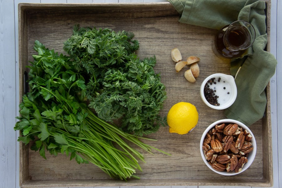 carrot greens, roasted garlic, lemon, pecans, and parsley on a tray with salt and pepper