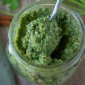a jar of carrot top pesto with a spoon in it