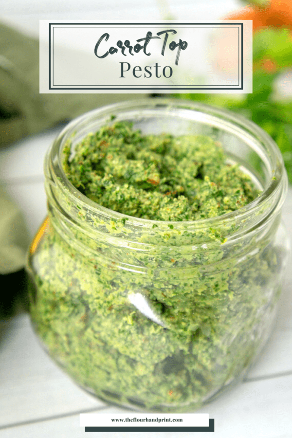 a small jar of carrot top pesto on a white table