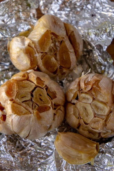 three bulbs of roasted garlic on foil