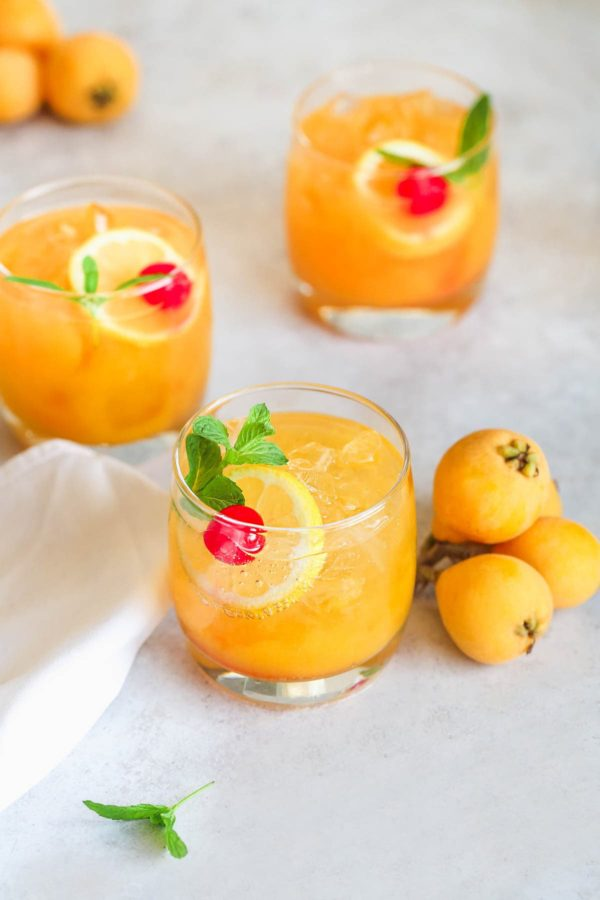 A loquat cocktail with lemon and a cherry from Little Sunny Kitchen