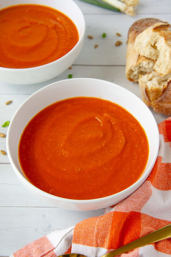 two bowls of carrot tomato soup with bread