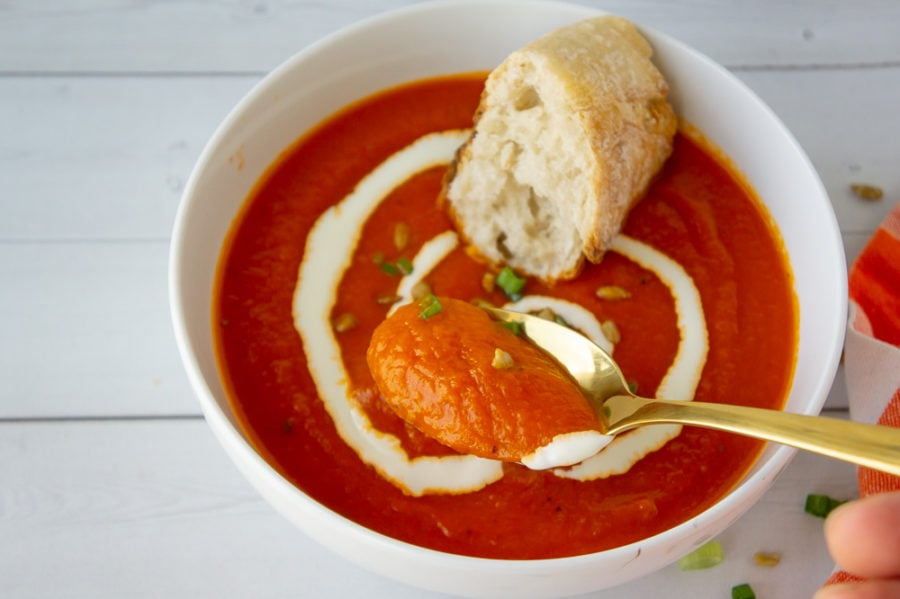 a bowl of carrot tomato soup with a swirl of yogurt and sunflower seeds