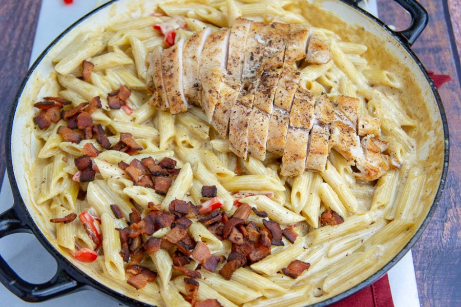 a wide pan of creamy chicken pasta with bacon and bell peppers