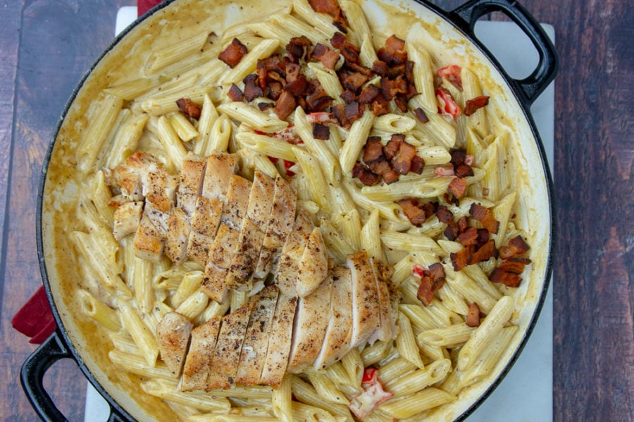 a large pan of penne pasta with chicken, bacon, peppers, and a creamy sauce