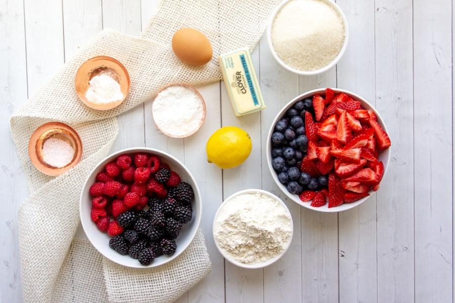 bowls of berries, with smaller bowls of sugar, baking powder, cornstarch, flour, butter, and salt