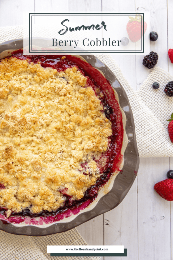 A berry cobbler on a white wooden table with burlap and fresh berries