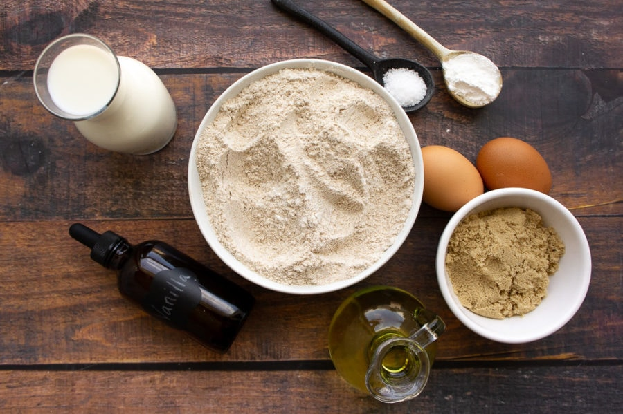 a bowl of whole wheat flour, brown sugar, with spoons of baking powder salt, vanilla, milk, and 2 eggs