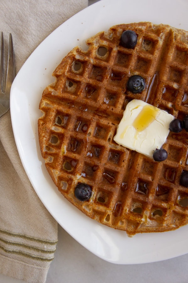 a waffle with blueberries butter and syrup on a white plate