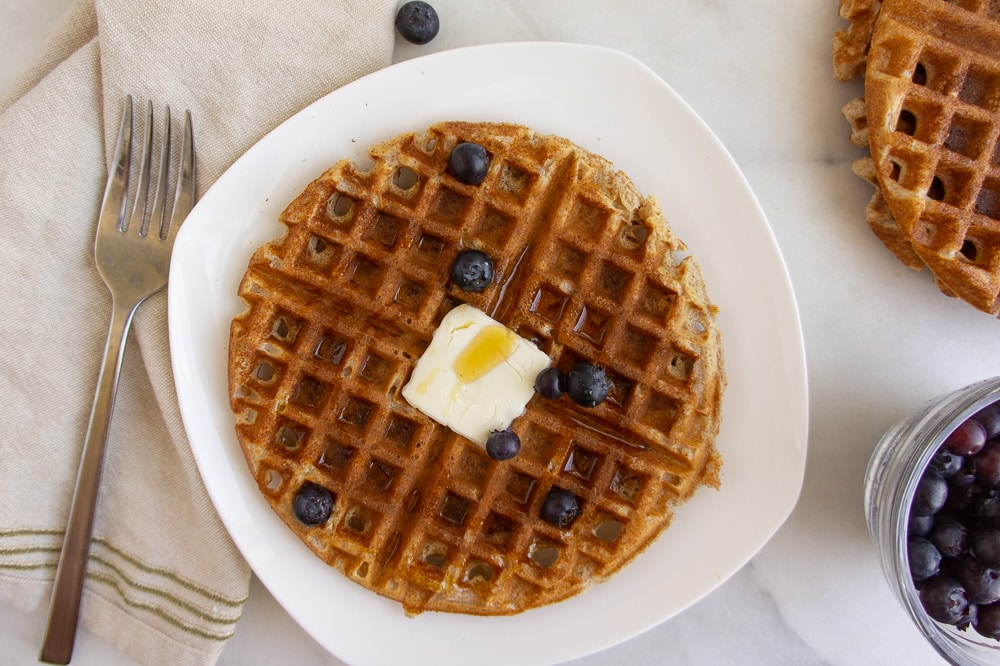a whole wheat waffle on a white plate next to a fork