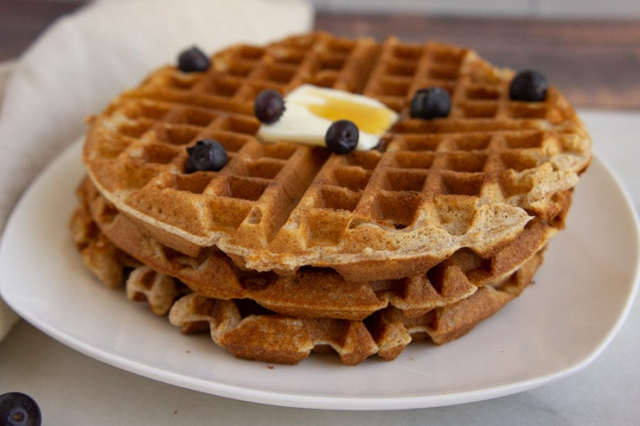 a stack of whole wheat waffles with butter and blueberries