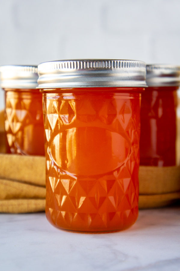 jars of apricot jelly on a white table