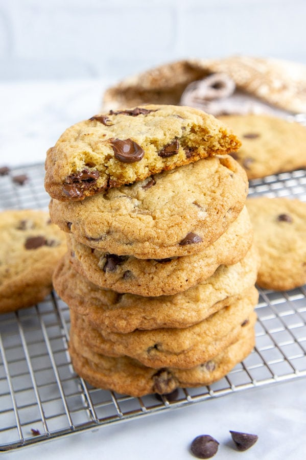 A stack of thick and chewy chocolate chip cookies on a metal cooking rack
