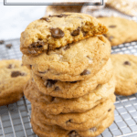 a stack of chocolate chip cookies with one broken in half