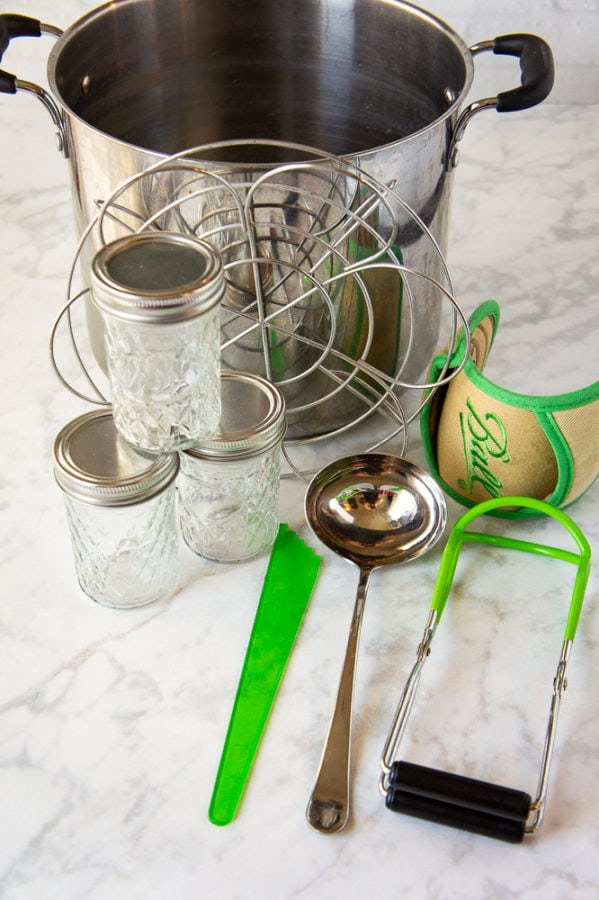 a pot with canning supplies arrange beside it