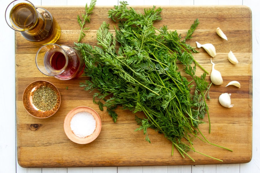 carrot greens on a board with salt, garlic, vinegar, oregano, and oil