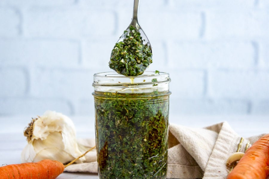 a jar and a spoon of chimichurri