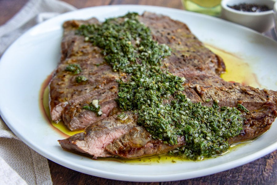 flank steak with chimichurri on a white plate