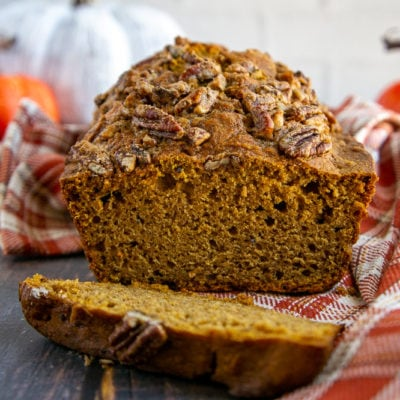 a healthy pumpkin bread loaf sliced on a wooden table