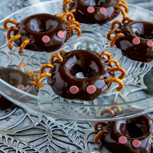 a platter of chocolate donuts decorated like spiders